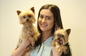 Member of Dunedin Staff Holding Two Identical Fluffy Dogs